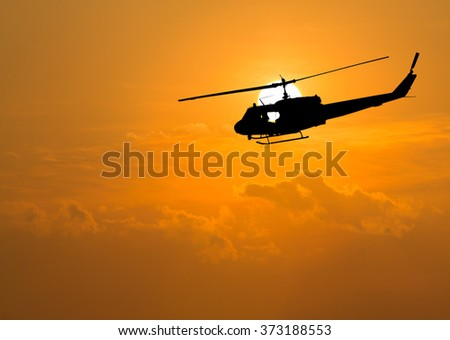 silhouette of helicopter with sunset. - stock photo