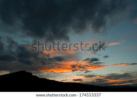 Silhouette of hill at sunset - stock photo