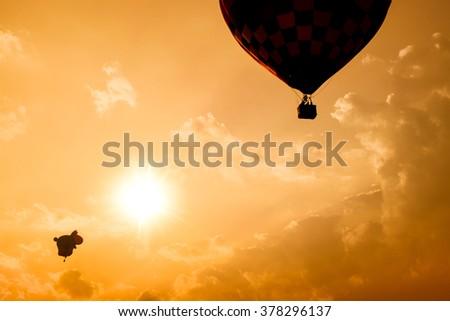 Silhouette of hot air balloon over mountain - stock photo