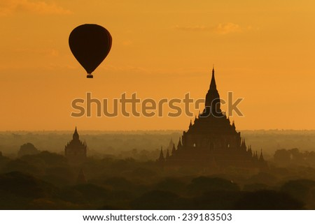 Silhouette of hot air balloon over pagoda temples of Bagan in misty morning, Myanmar - stock photo