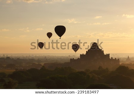 Silhouette of hot air balloons over pagoda temples of Bagan in misty morning, Myanmar - stock photo
