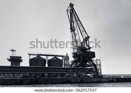 Silhouette of industrial crane in Balchik port, Bulgaria. Dark blue toned monochrome stylized photo - stock photo