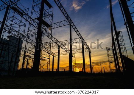 Silhouette of iron construction at sunset time. worker empty. - stock photo