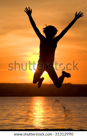 Silhouette of joyful guy jumping with raised arms near lake at sunset - stock photo