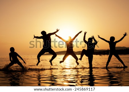 Silhouette of kids jumping on the beach on beautiful summer sunset - stock photo