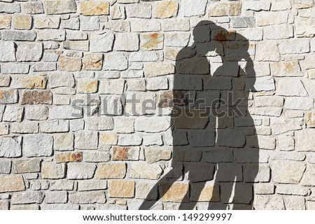 Silhouette of kissing couple, against natural stone wall - stock photo
