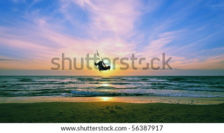 silhouette of kite surfer jumping to the sky - stock photo