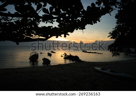 silhouette of little boats and people in the sea, sunset time - stock photo