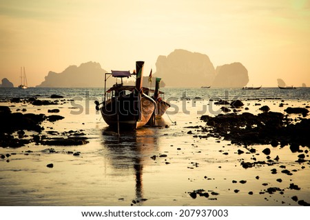 Silhouette of longtail boat at sunset at Railay beach, Thailand - stock photo
