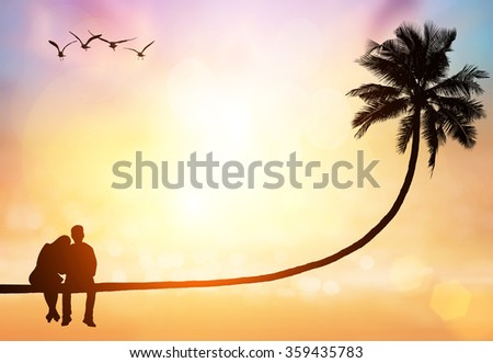 silhouette of love couple sit on  coconut tree on sunset sky - stock photo