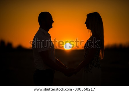 Silhouette of lovers against the backdrop of the setting sun - stock photo