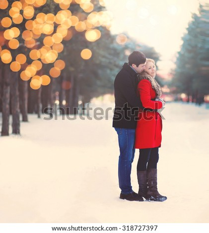 Silhouette of loving couple embracing in warm winter day with lights bokeh, vintage colors - stock photo
