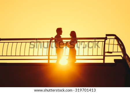 Silhouette of loving couple standing on a footbridge against the sunset. - stock photo