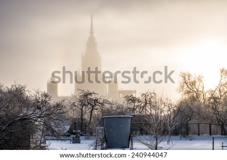 Silhouette of main building of Lomonosov Moscow State University in winter frosty fog at sunset. Sparrow Hills, Moscow, Russia. The highest among seven Stalin's soviet skyscrapers built in mid-20th. - stock photo