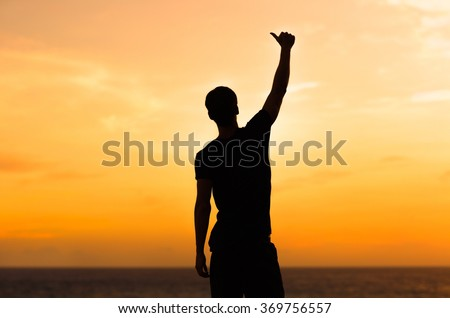 Silhouette of male celebrating with arm up towards the sunrise. Achievement concept.  - stock photo