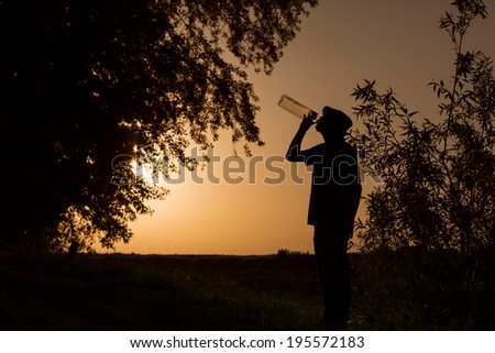 Silhouette of man at sunset drinking alcohol in bushes - stock photo