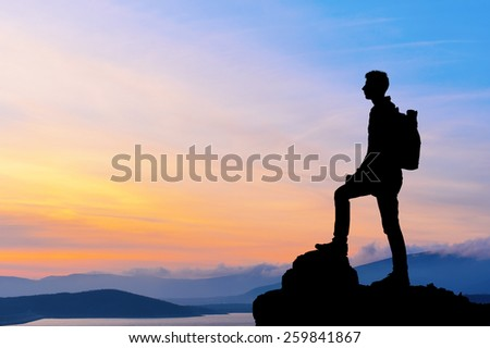 Silhouette of man at the top of the mountain on sunset. Beautiful landscape. - stock photo
