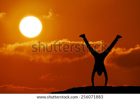 Silhouette of man at the top of the mountain on sunset. Man stands on his hands at the top of the mountain. Beautiful landscape. - stock photo
