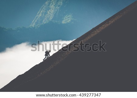 silhouette of man climbing steep mountain. Good image for adventure, struggle and success story photo. - stock photo