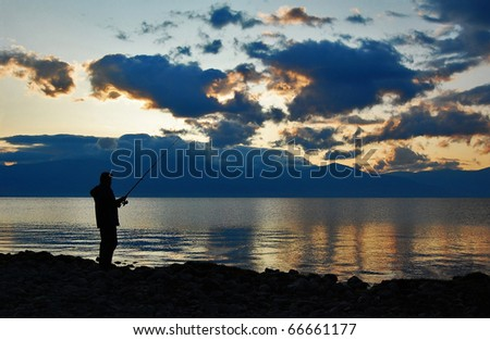 Silhouette of Man Fishing at Sunrise - stock photo