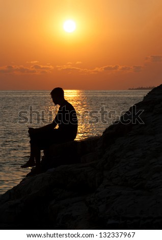 Silhouette of man from side sitting on a rock and enjoying the sunset - stock photo