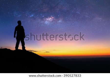 Silhouette of man is standing on top of mountain and enjoy to see the milky way before sunrise. - stock photo