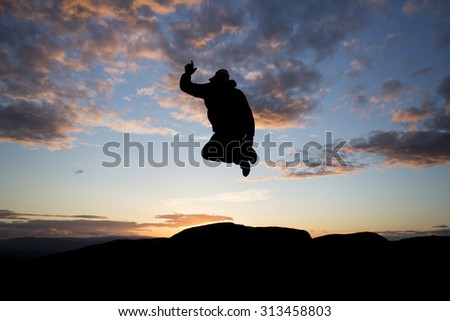 silhouette of man jumping at sunset - stock photo