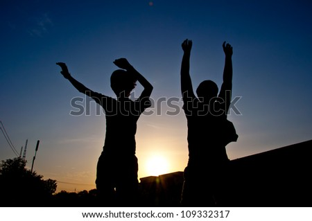 silhouette of man jumping for victory - stock photo
