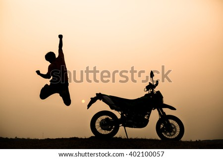 Silhouette of man jumping on the background of motorcycle and sunset - stock photo