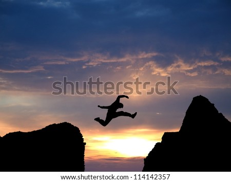 silhouette of man jumping over rocks in sunset - stock photo