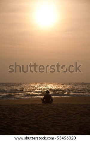 silhouette of man making yoga in meditation pose on sunset beach - stock photo
