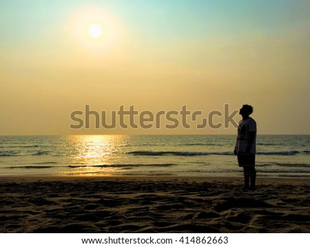 Silhouette of man on beach and sun, sunset time. Young man looking at sunset sun on beach. Silhouette of man on beach at sunset, Silhouette of man by sea, Silhouette of man on beach background image - stock photo