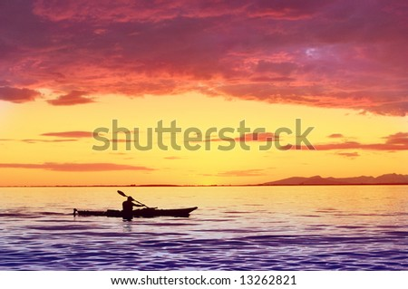 silhouette of man on kayak with sunset - stock photo