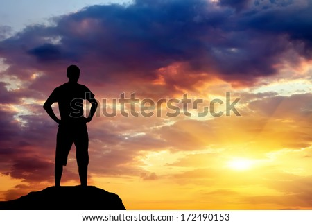 Silhouette of man on rock at sunset. Man on top of mountain. Conceptual design.  - stock photo