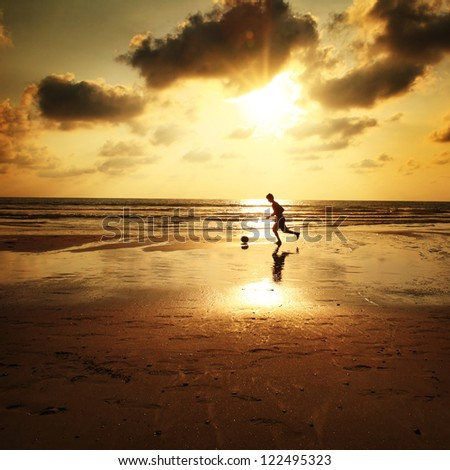 Silhouette of man playing football on the beach - stock photo