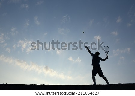 Silhouette of man playing tennis - stock photo