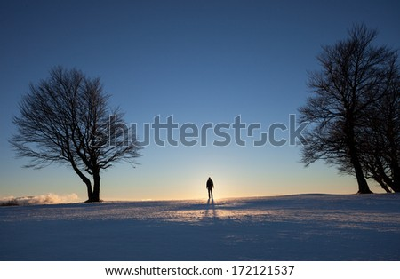 silhouette of man standing in winter landscape  - stock photo