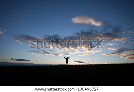 silhouette of man standing on field in front of blue sky  - stock photo
