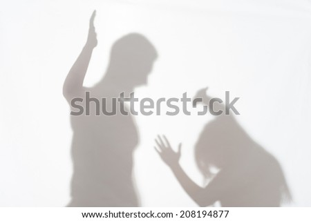 Silhouette of man striking the woman who cannot to protect herself - stock photo