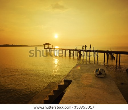 silhouette of man walking at the jetty during golden sunset - stock photo