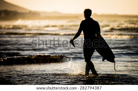 Silhouette of man with a surfboard on the beach - stock photo