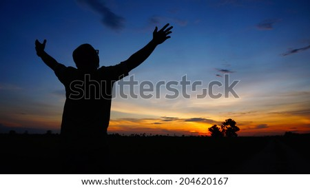 Silhouette of man with arms wide open during sunset - stock photo