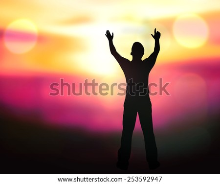 Silhouette of man with hands raised to blurred beautiful sunset background. - stock photo