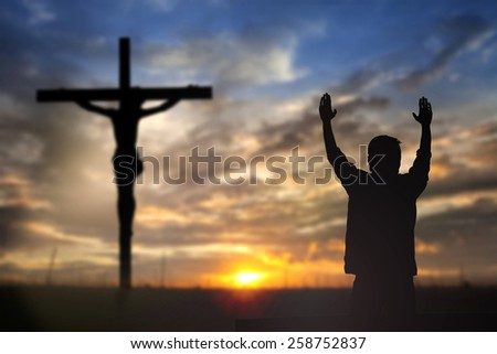 Silhouette of man with raised hands over blur cross concept for religion, worship, prayer and praise. - stock photo