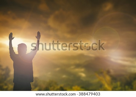 Silhouette of man with raised hands over blur sea concept for religion, worship, prayer and praise. sunset sunrise light beautiful quran life freedom peace appeal psalm bible pray for France halloween - stock photo