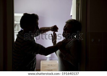 Silhouette of mature couple fighting, the man is physically abusing woman. Woman is victim of domestic violence - stock photo