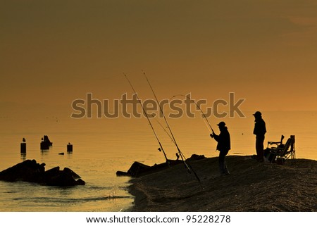 silhouette of men fishing on the bay early morning - stock photo