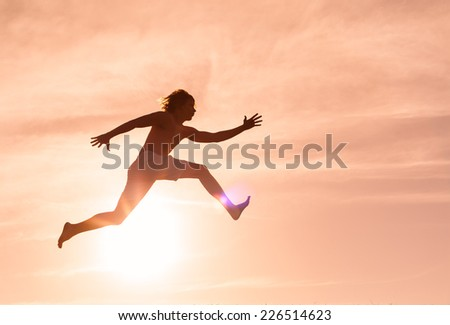 Silhouette of men jumping through the air - stock photo