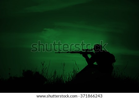Silhouette of military sniper with weapons at night. night vision concept - stock photo