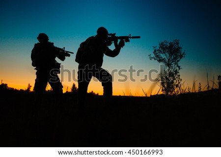 Silhouette of military soldiers with weapons at night. shot, holding gun, colorful sky. military concept. - stock photo